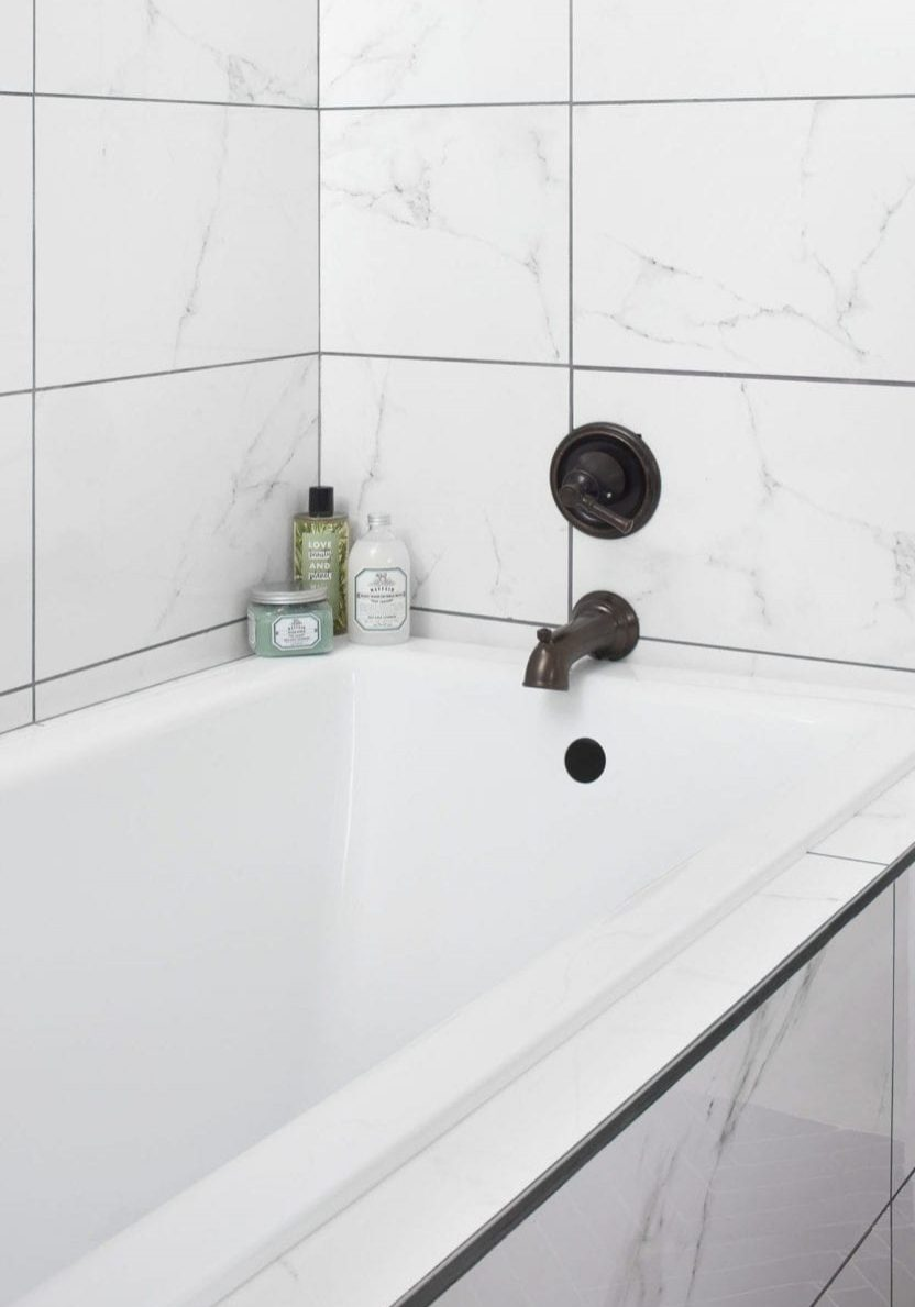 Unwind in the serene bathroom composed of natural elegance and voluptuousness of quartz countertops, marbleized walls, and porcelain floor tiles